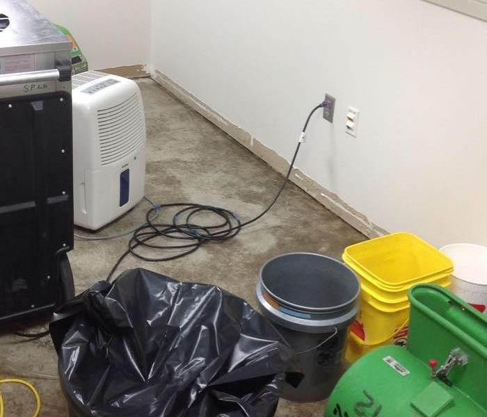 A large dehumidifier and fan are lined up on the floor, ready to dry up the unwanted water.
