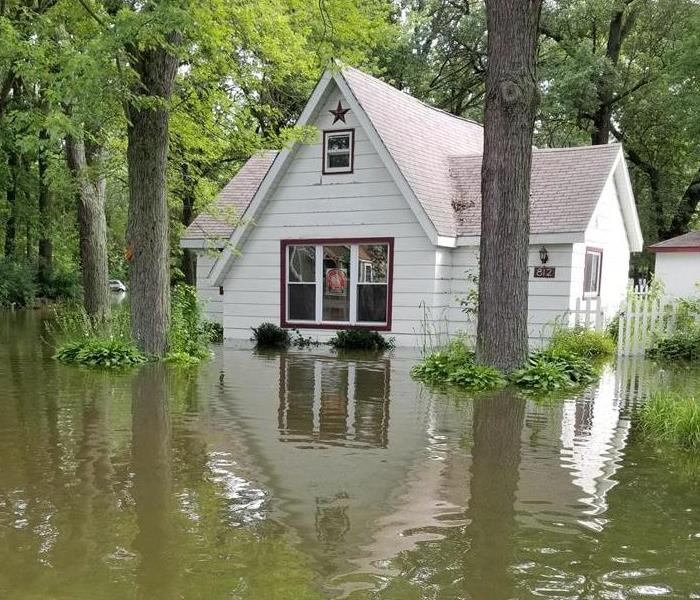 Water surrounds the property of a Wisconsin home. Trees bases and grass submerged in water.
